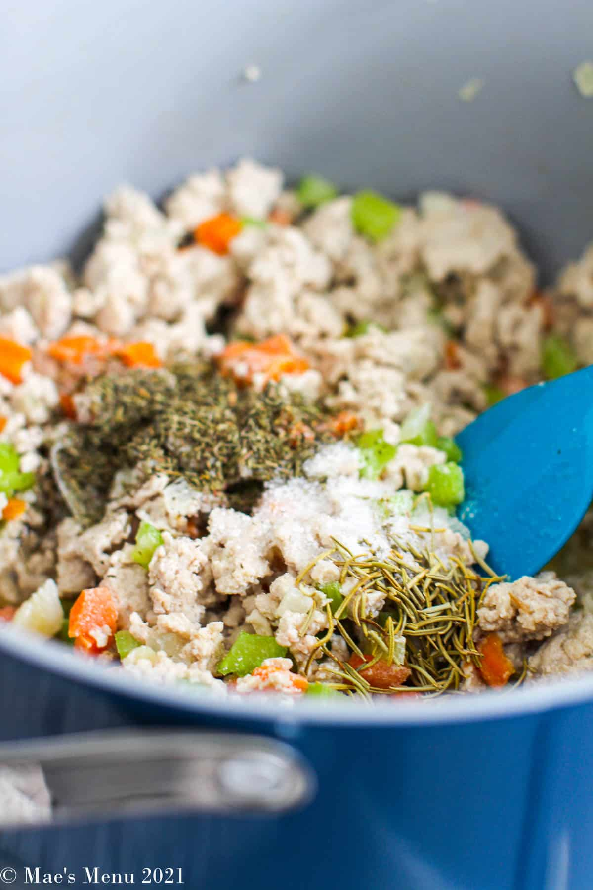 Add the seasonings to the pot with the sauteed chicken and veggies