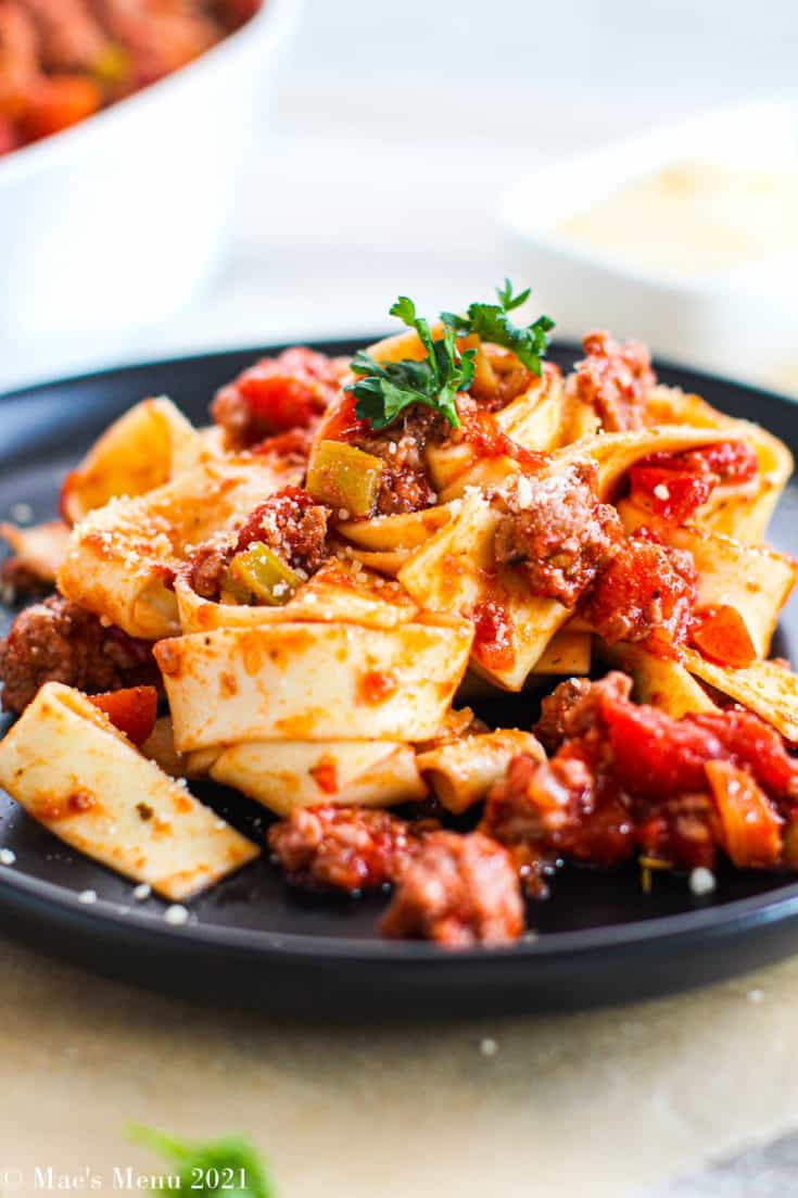 An up-close shot of chicken bolognese with a bowl of the sauce in the background