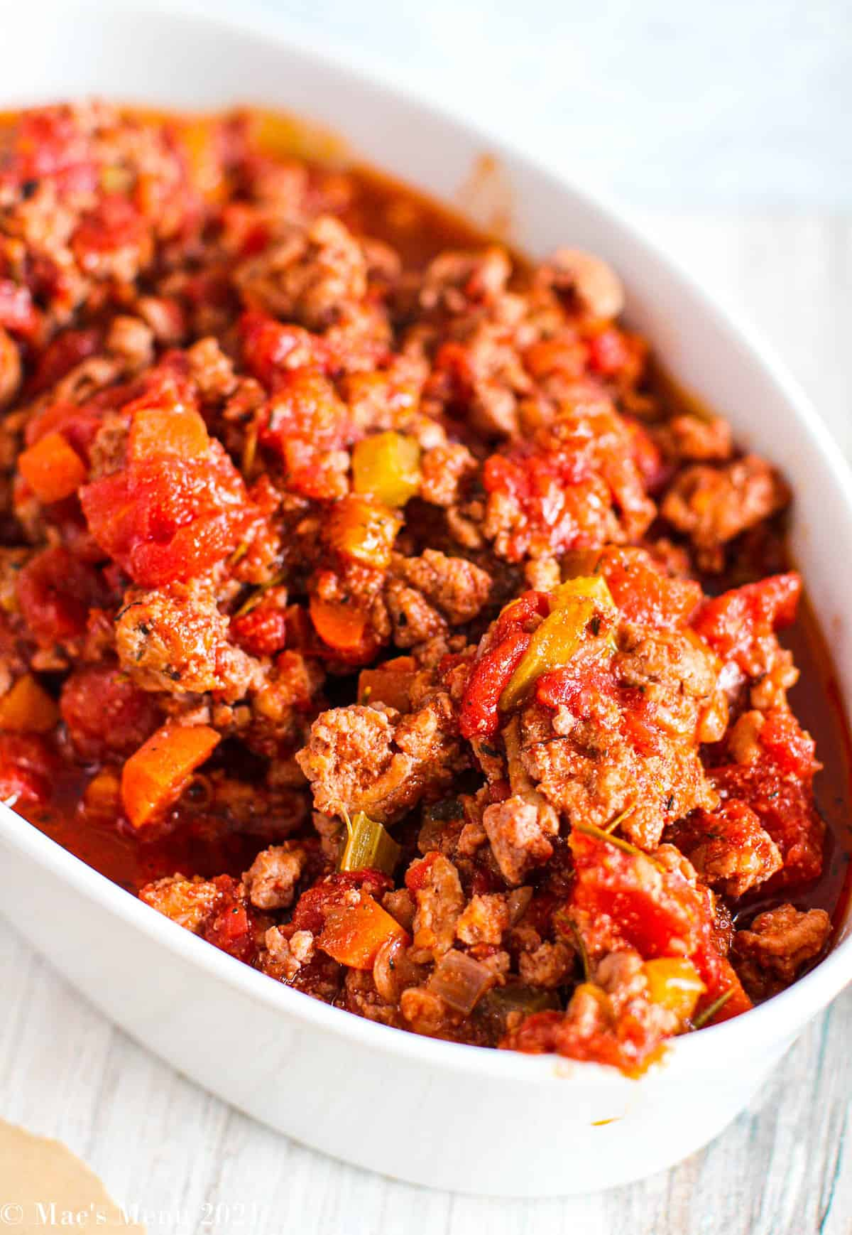An up-close side shot of chicken bolognese in a white dish