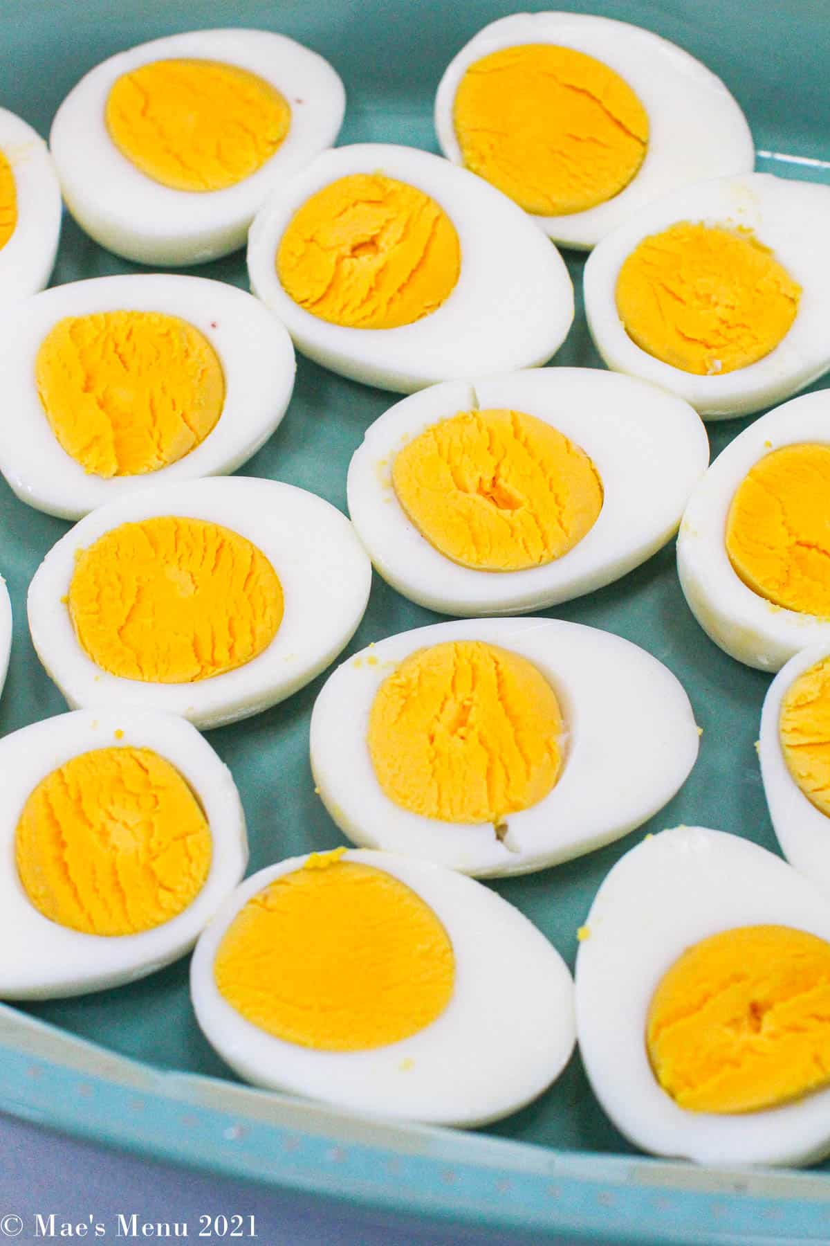 A blue plate of hard-boiled eggs, peeled and cut in half