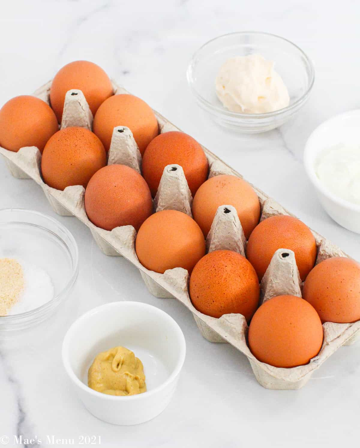 All the ingredients for healthy deviled eggs:  large eggs, mayonnaise, greek yogurt, dijon mustard, and onion powder and salt