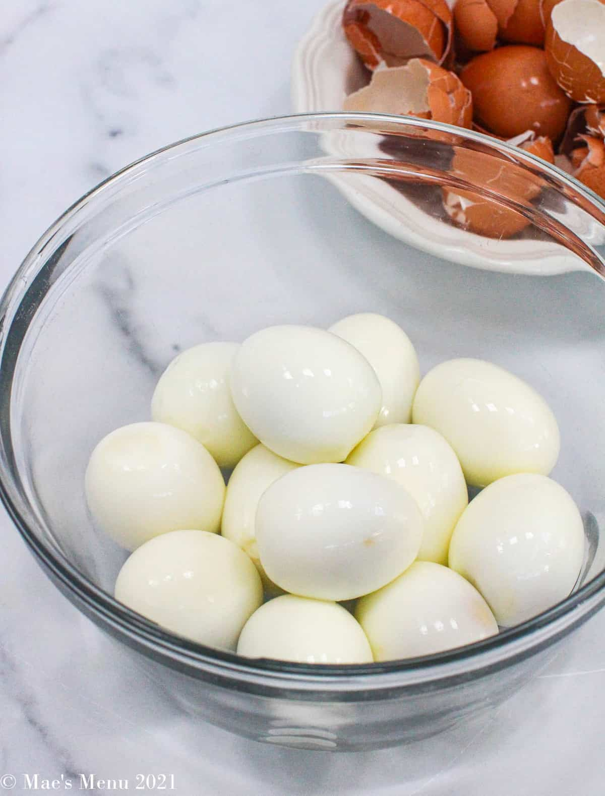 A side shot of a glass bowl of hard boiled eggs