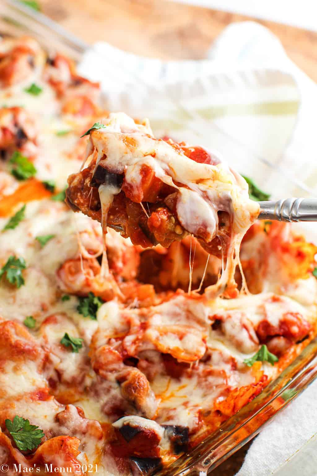A large spoonful of the italian sausage casserole with strings of cheese hanging down