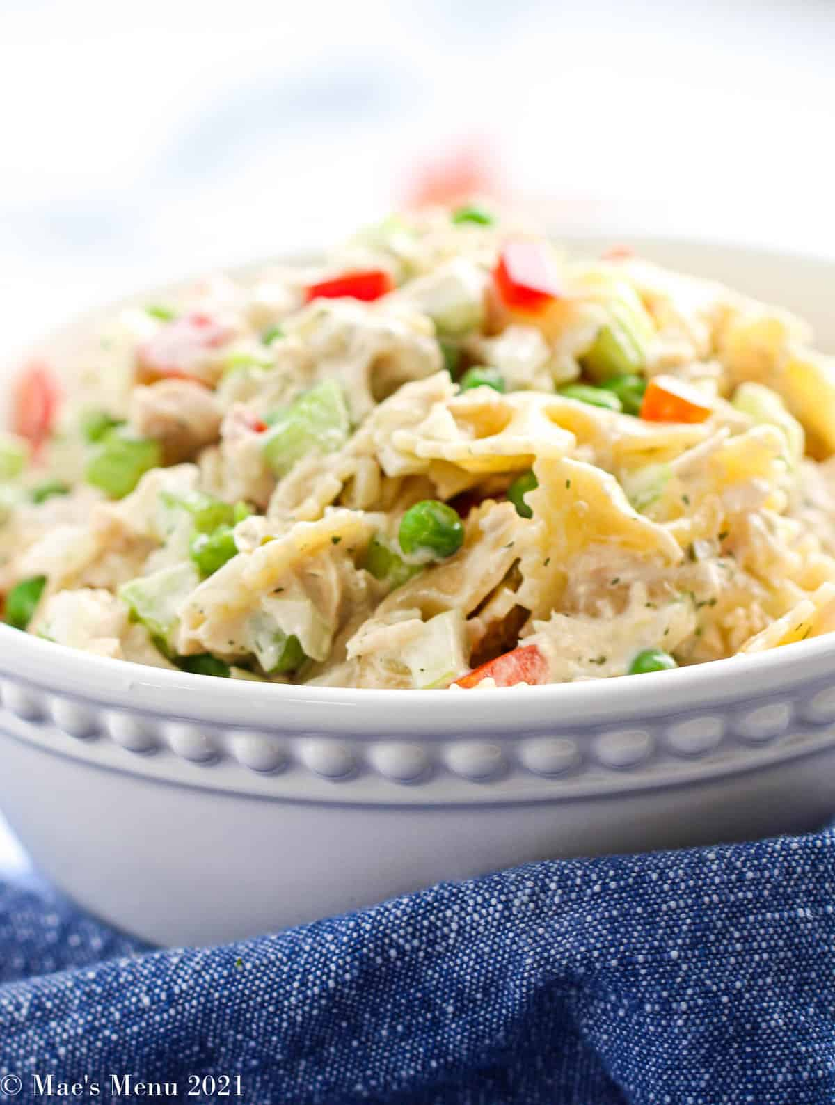 A side shot of a large serving bowl of tuna macaroni salad