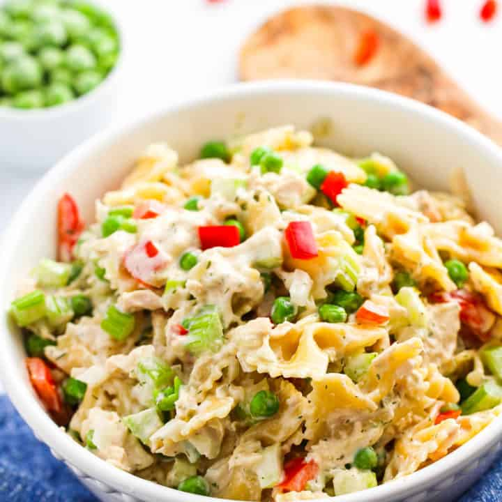 A large white bowl of tuna macaroni salad with wooden tongs in the background