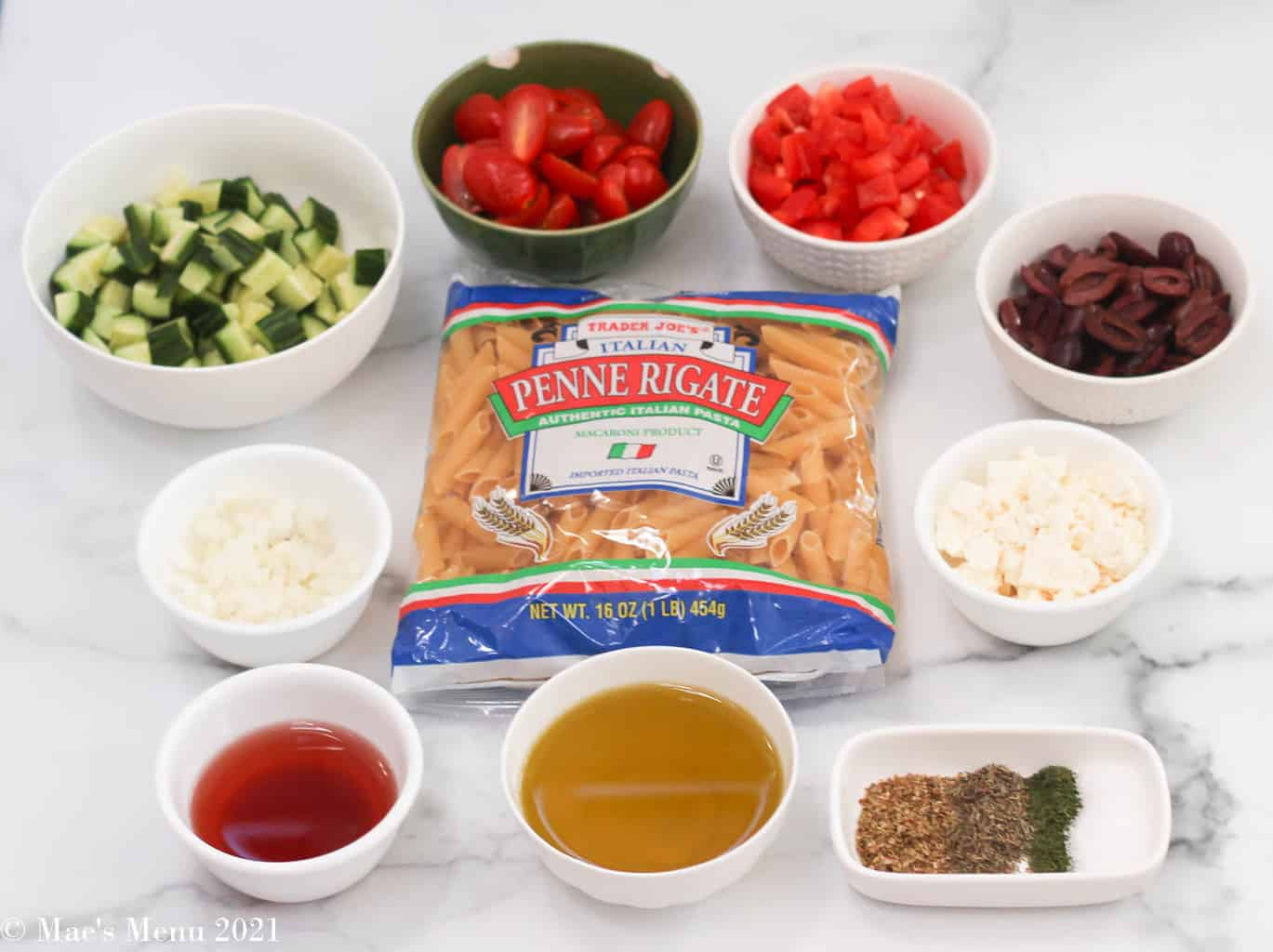 All the ingredients for Greek penne pasta salad on a granite counter