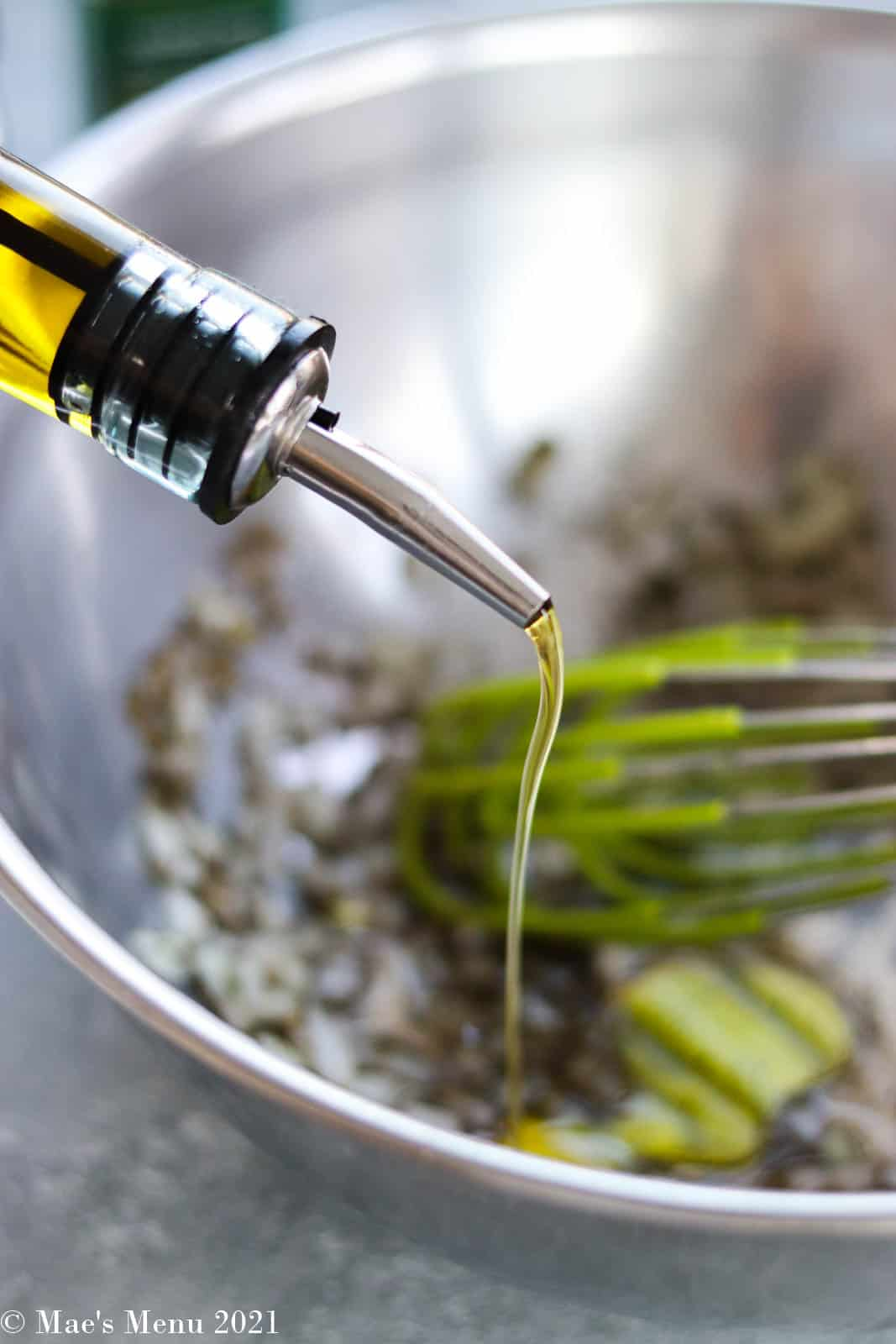 Whisking the olive oil into the salad dressing