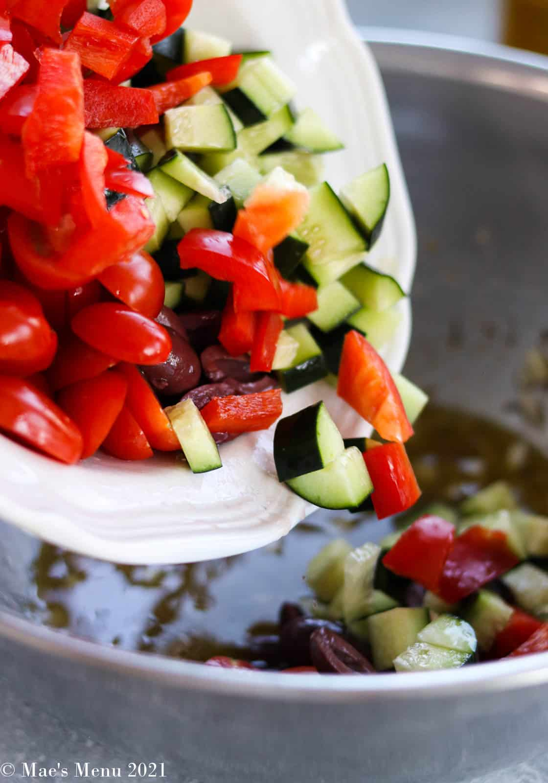 Adding the chopped vegetables to the greek salad dressing