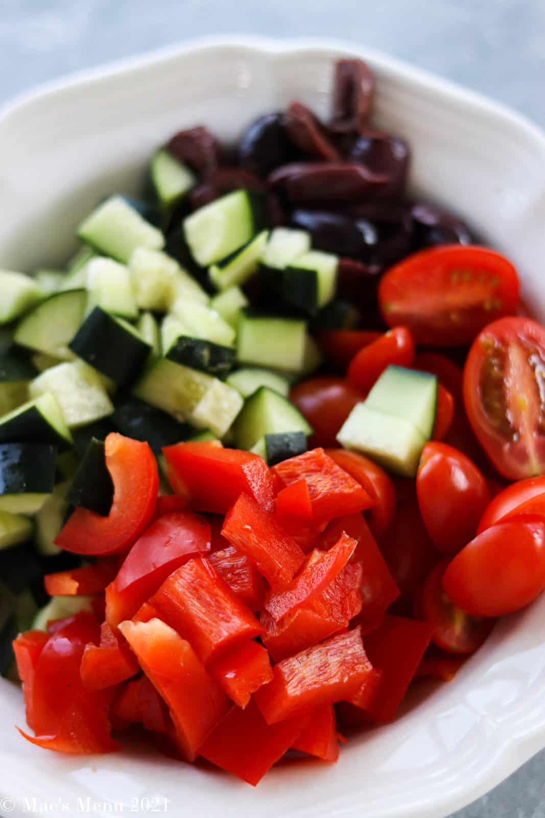a white bowl full of chopped veggies
