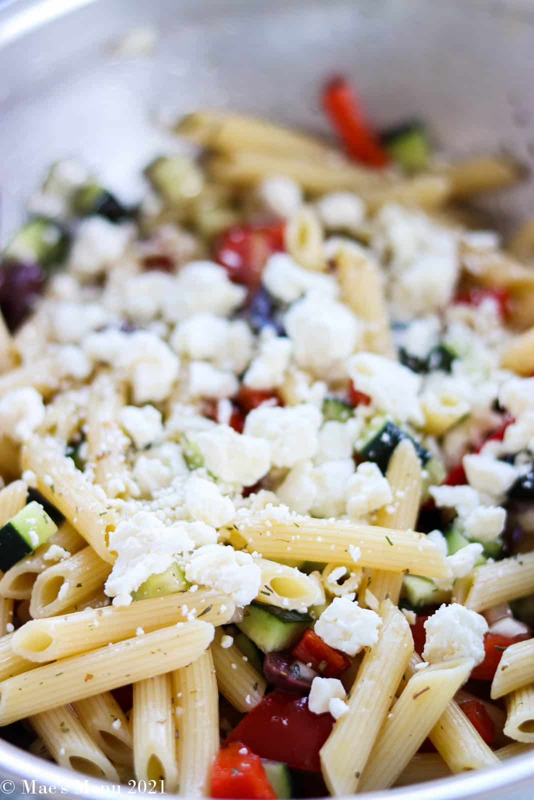 A large mixing bowl full of greek pasta salad with feta cheese sprinkled on top