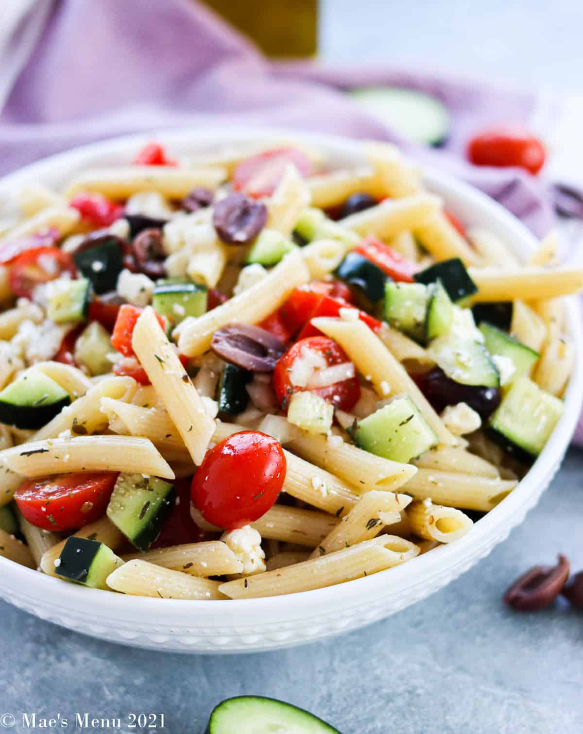 A side shot of a white bowl of Greek pasta salad surrounded by chopped vegetables