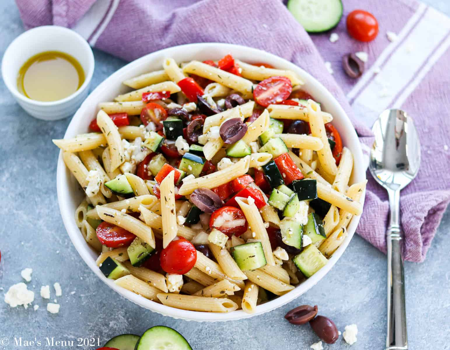 An overhead shot of a bowl of Greek Penne pasta slad surrounded by veggies, spoons, etc.