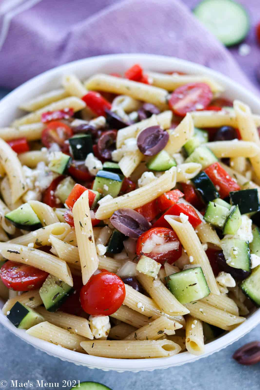 An overhead shot of a white bwol of Greek pasta salad