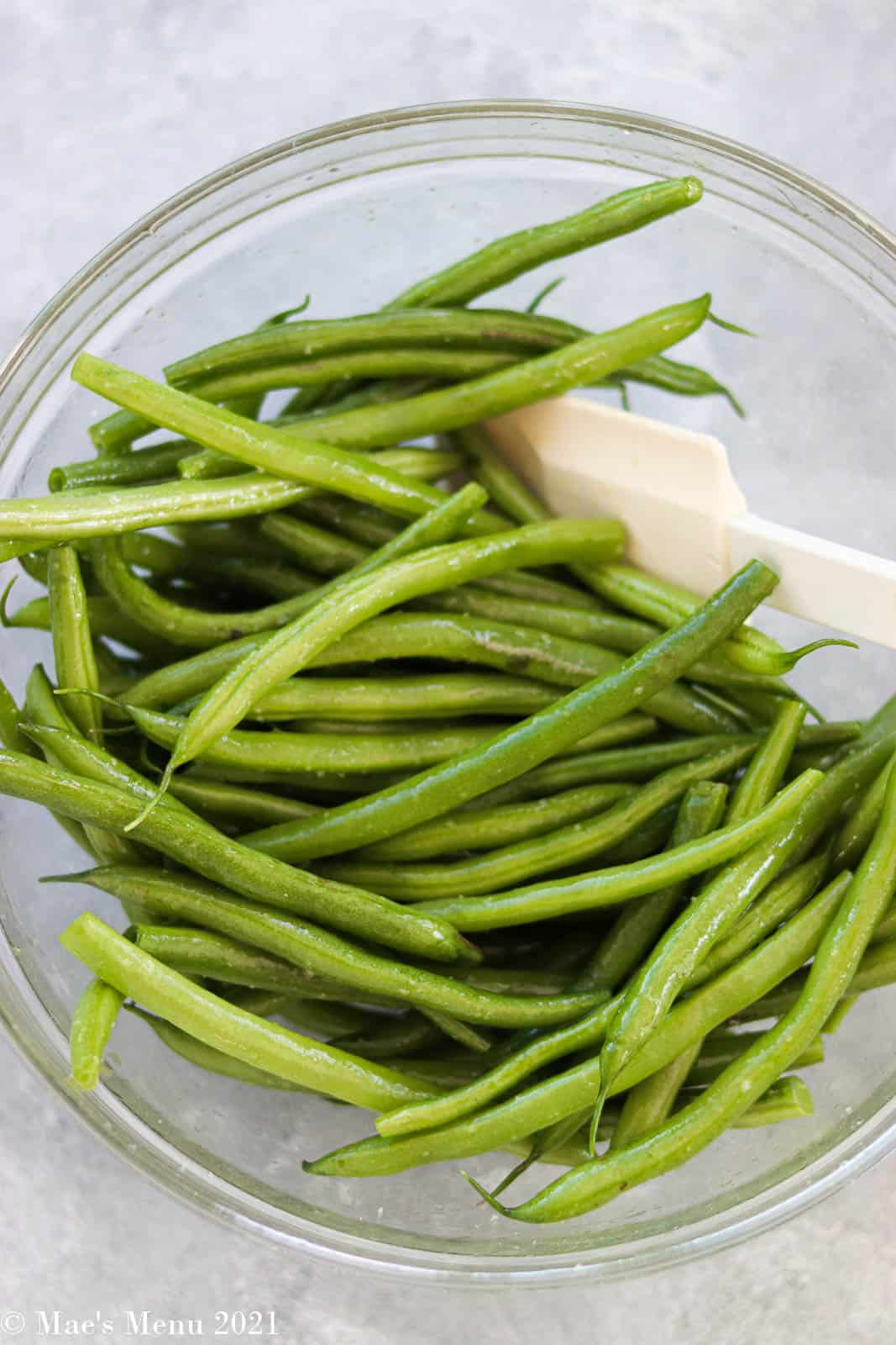 Tossing green beans with olive oil in a mixing bowl