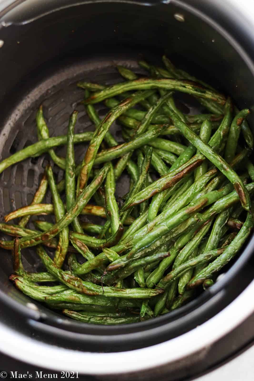 blistered Air fryer green beans in the basket of an air fryer