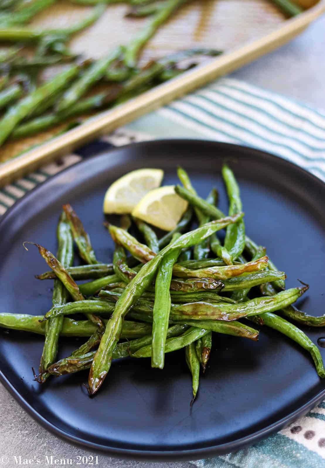 A side shot of a black plate of air fryer green beans with lemon