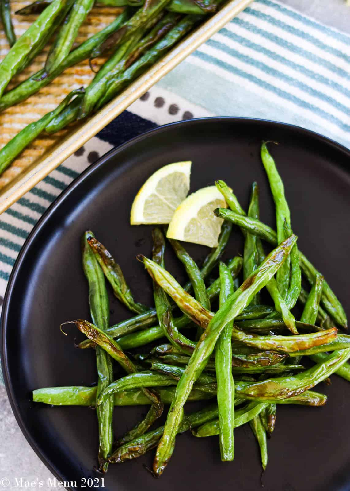 An overhead shot of a plate of air fryer green beans next to a sheet pan of the beans
