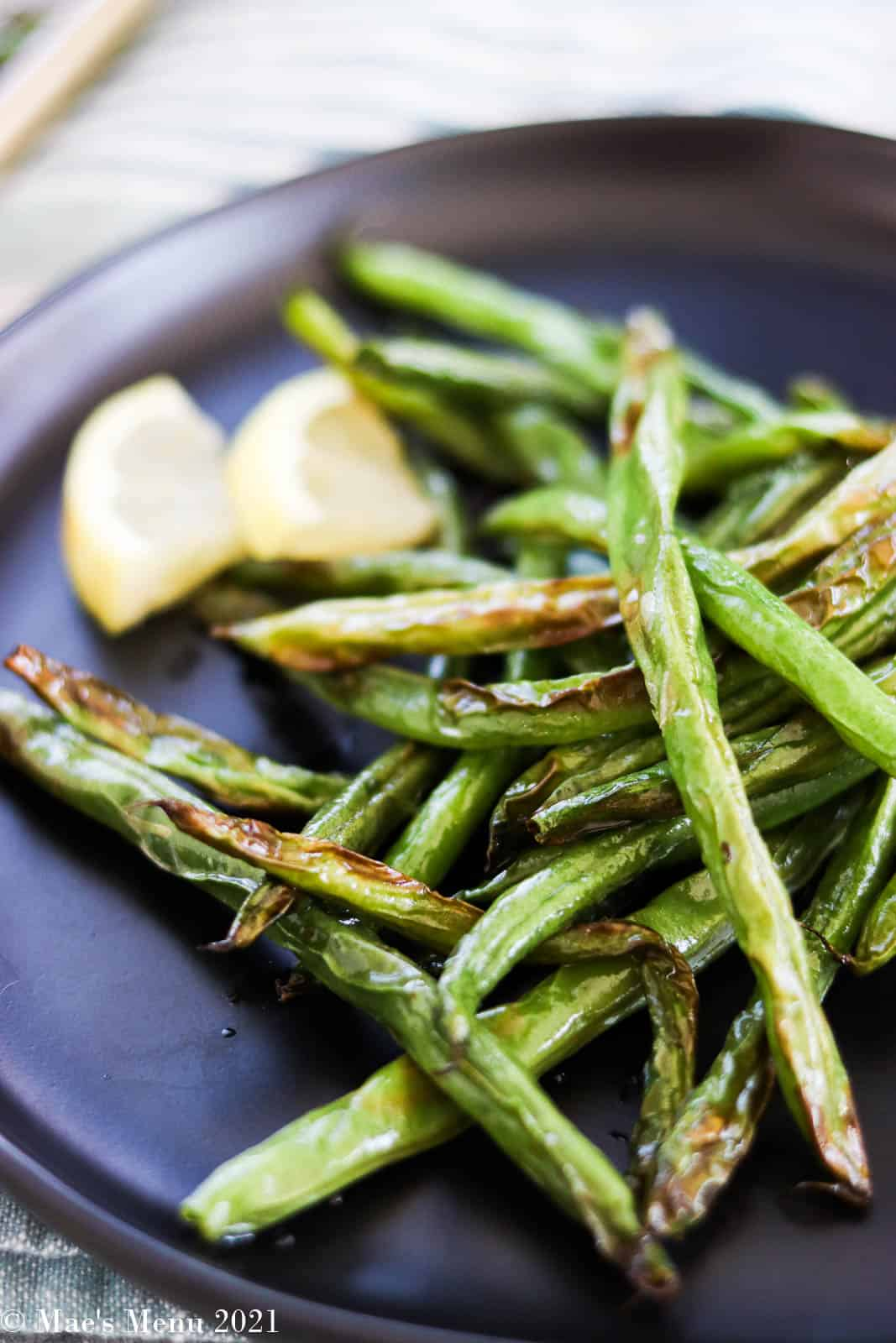 An up-close shot of a black plate of air fryer green beans with lemon