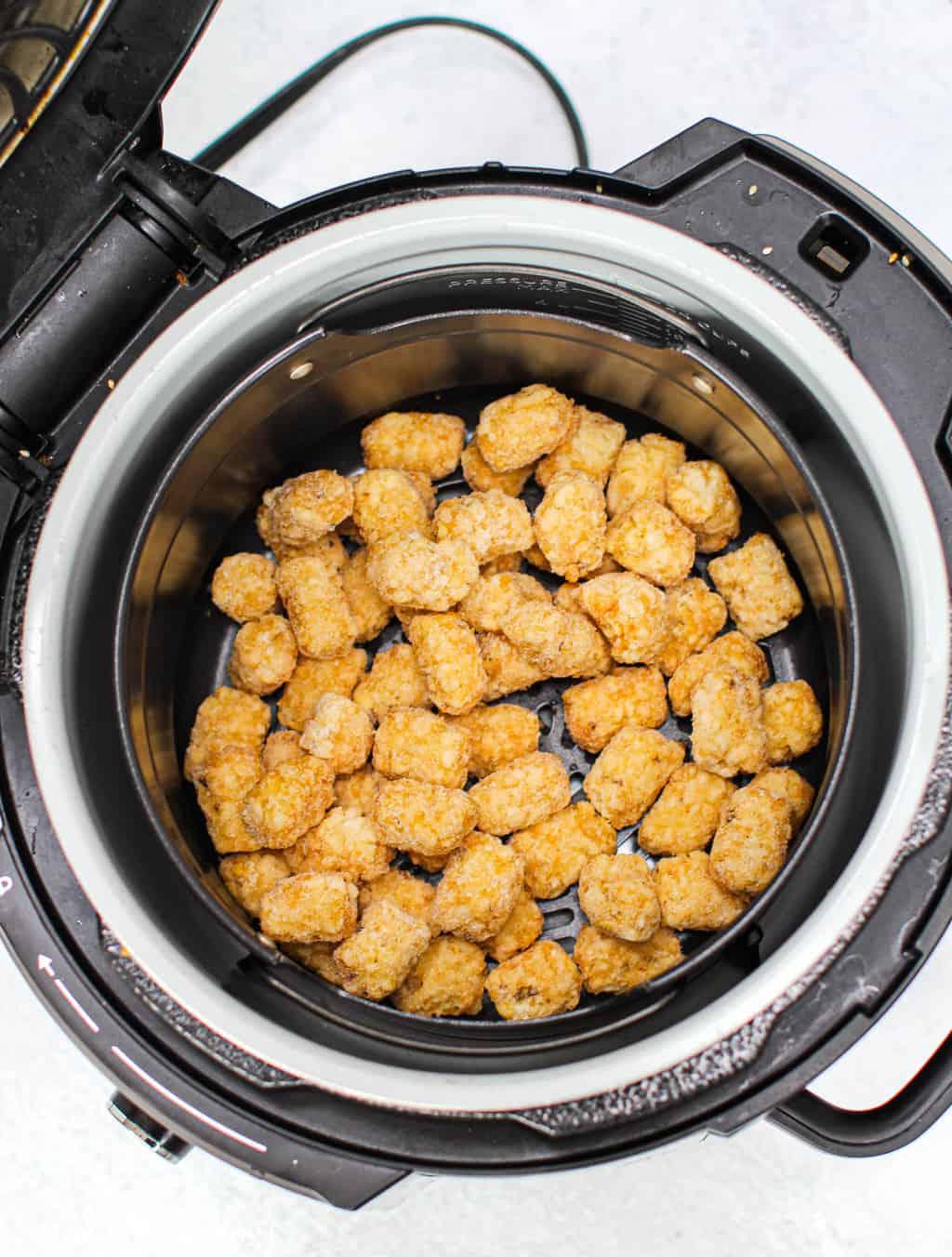 Frozen tater tots in an air fryer basket