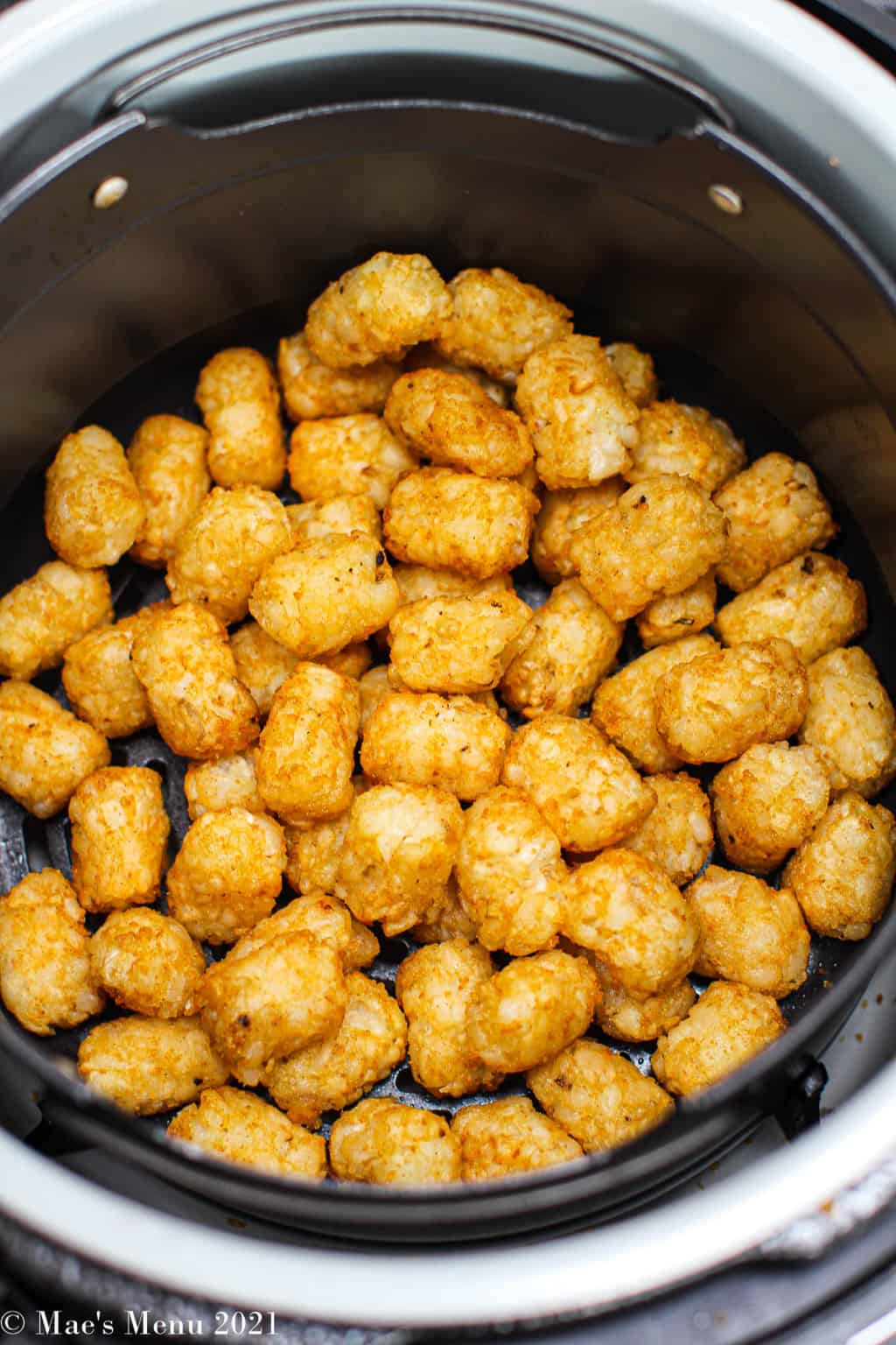 Tater tots cooking in an air fryer basket