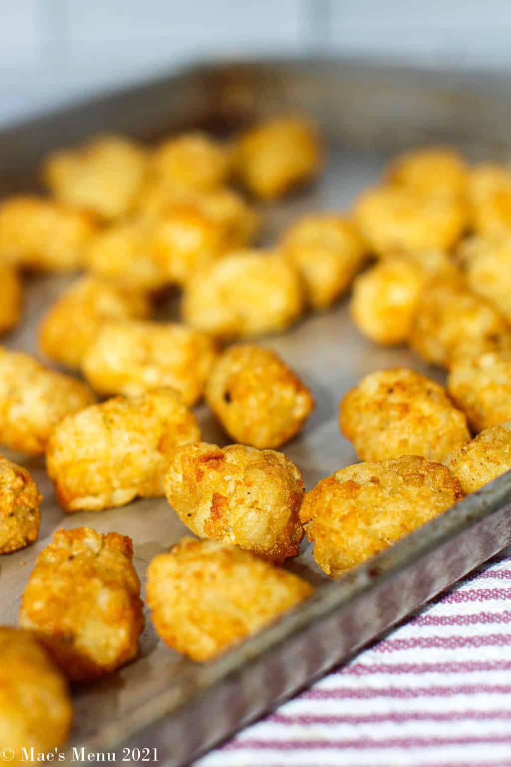 A side shot of air fryer tater tots on a cookie sheet
