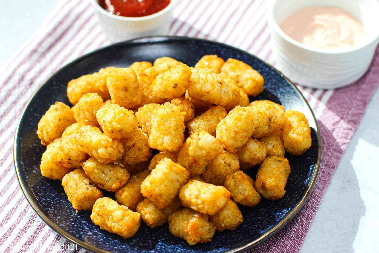 A Blue dish of air fryer tater tots with a cup of ketchup and aioli in the background