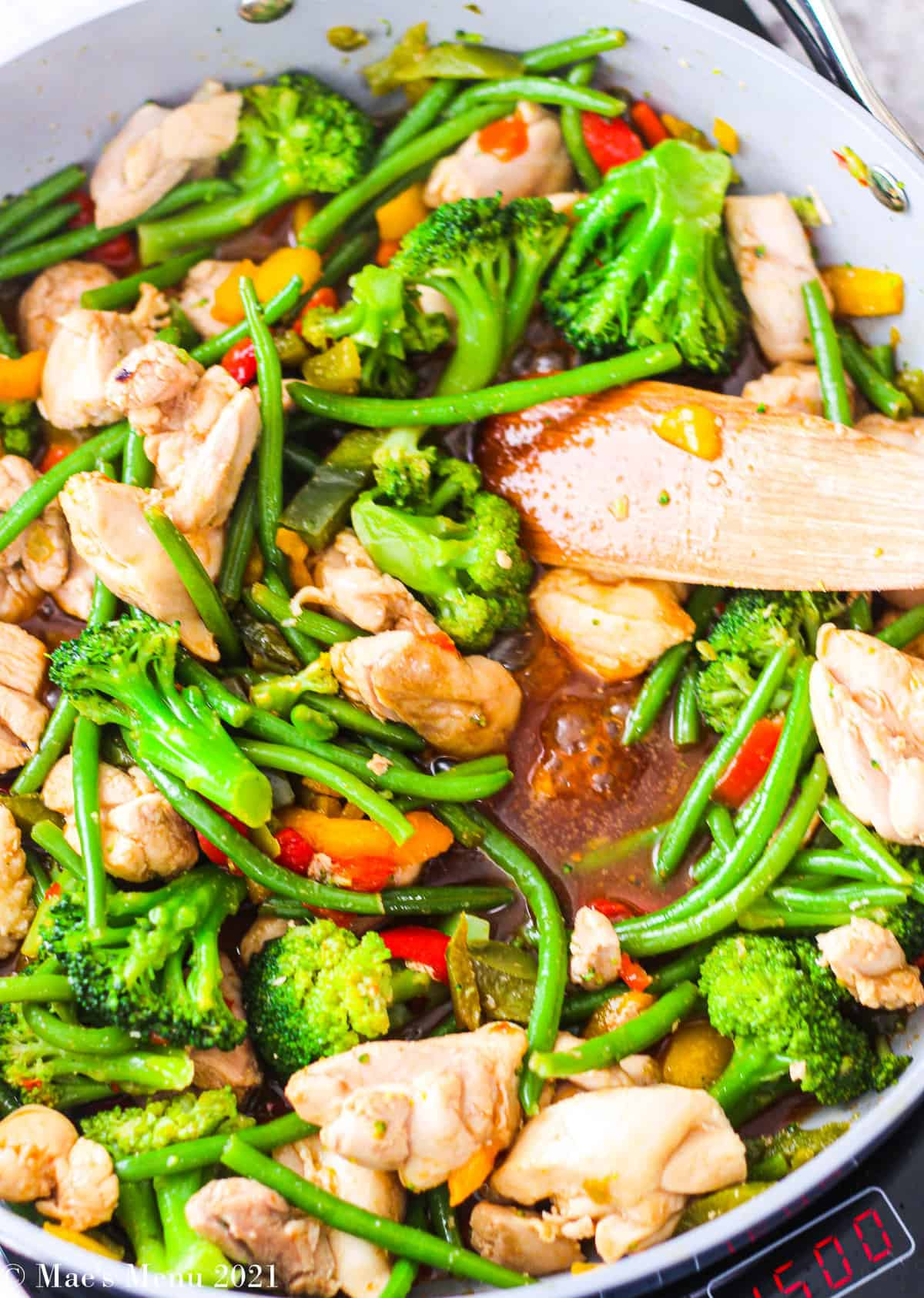 chicken and veggies simmering in a stir-fry sauce in a skillet