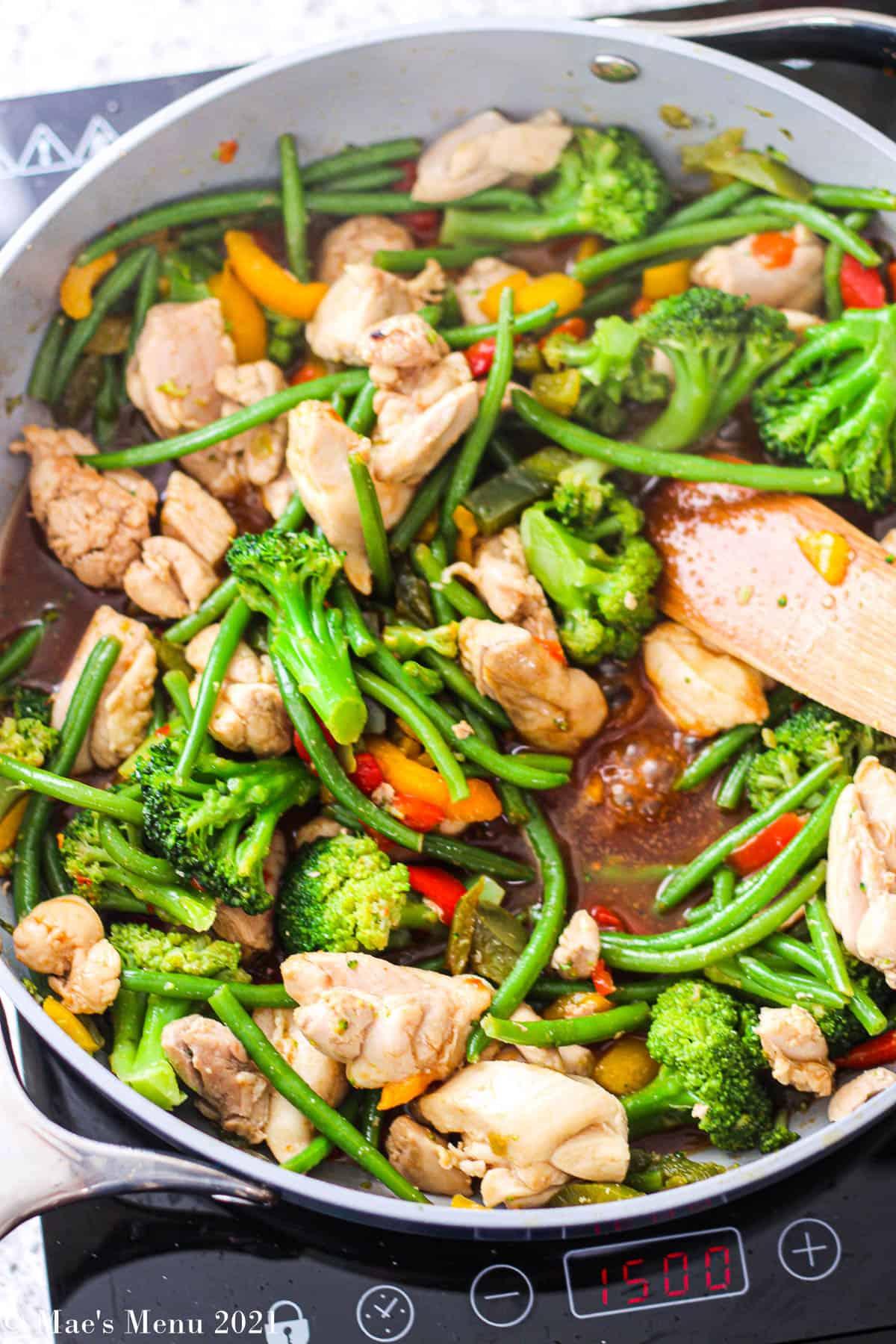 An overhead shot of a pan of chicken and frozen vegetable stir-fry