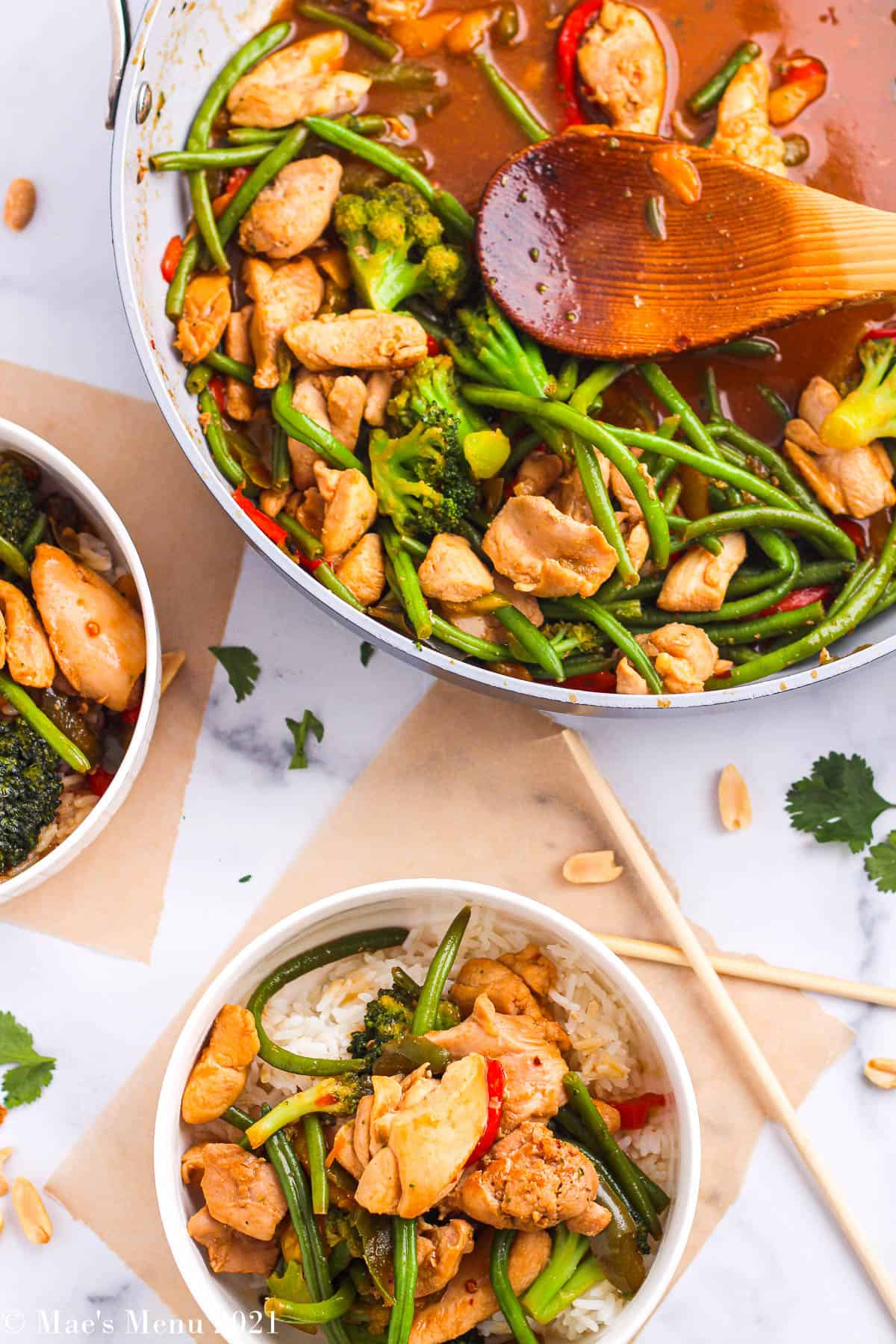 An overhead shot of a pan and 2 bowls of chicken stir-fry