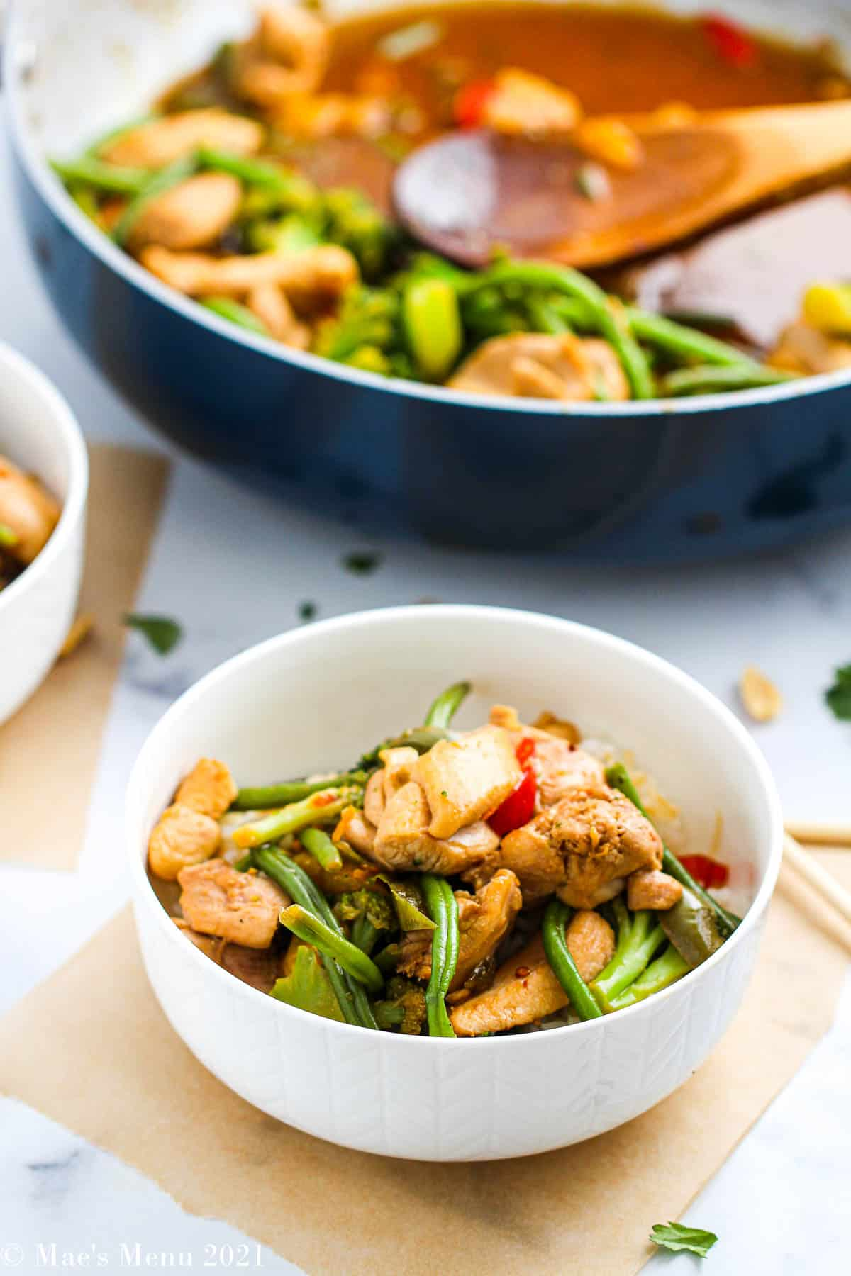An up-close shot of a chicken and frozen vegetable stir-fry in a bowl with a pan in the background