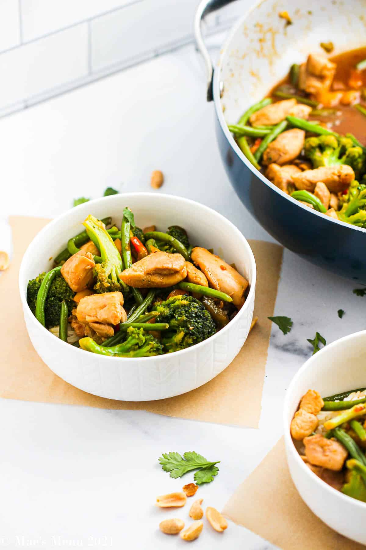 2 bowls of chicken stir-fry with frozen veggies on a granite countertop