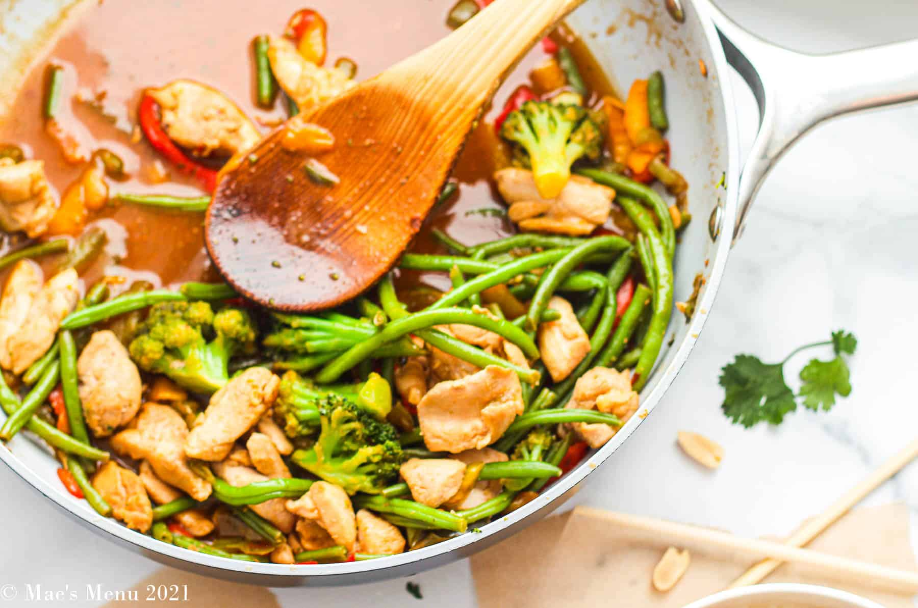 an overhead shot of a pan full of stir fry chicken with frozen vegetables
