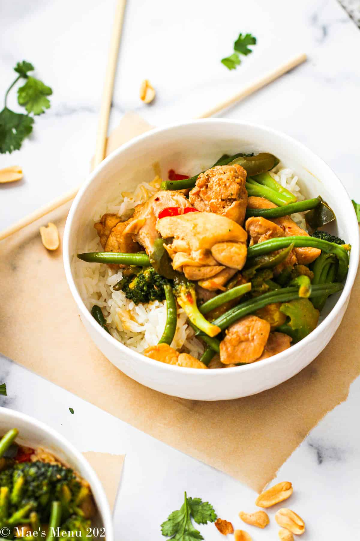 An up-close bowl of chicken and vegetable stir fry in a white bowl