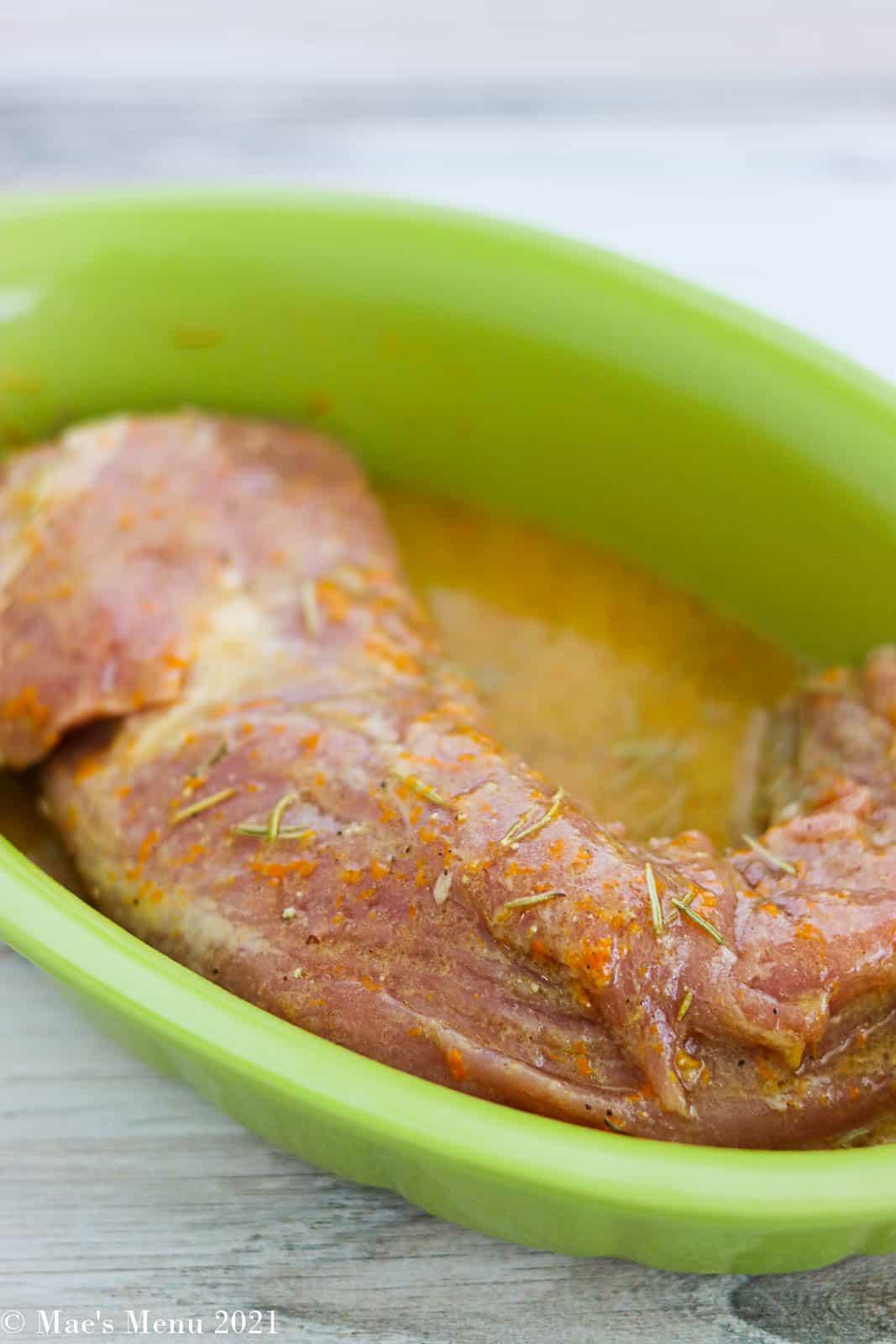 A baking dish with pork tenderloin  in the dijon marinade