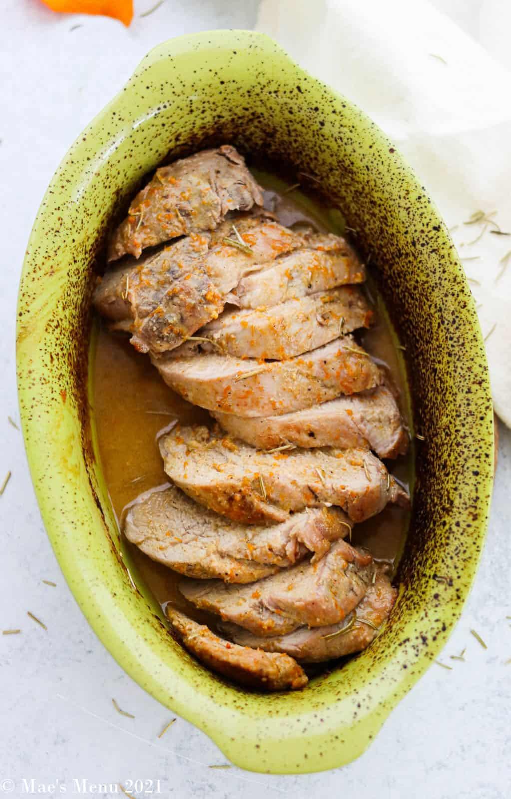 An overhead vertical shot of a pan of roasted dijon pork tenderloin in marinade