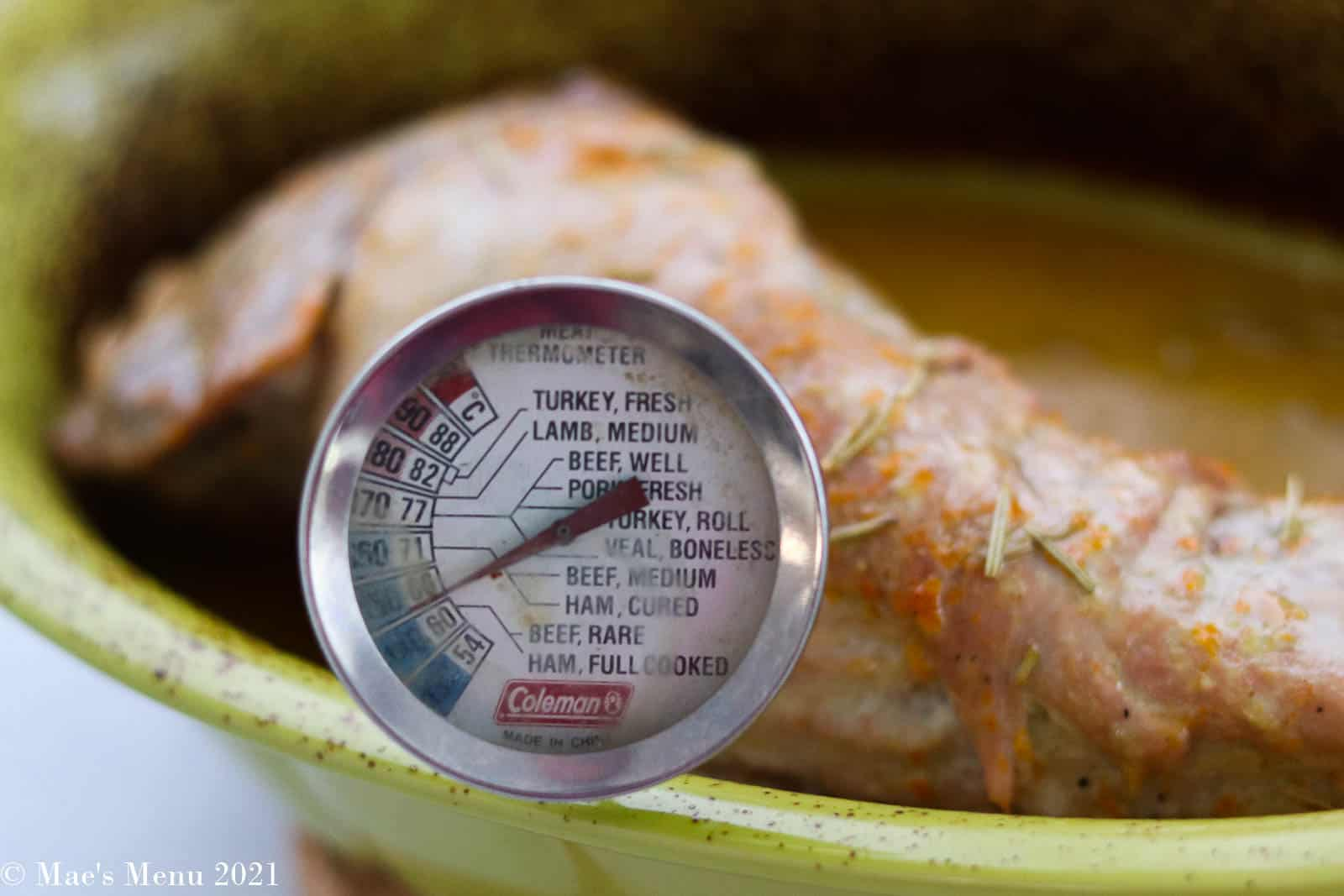 an up-close shot of Roasted dijon pork tenderloin with a thermometer in it