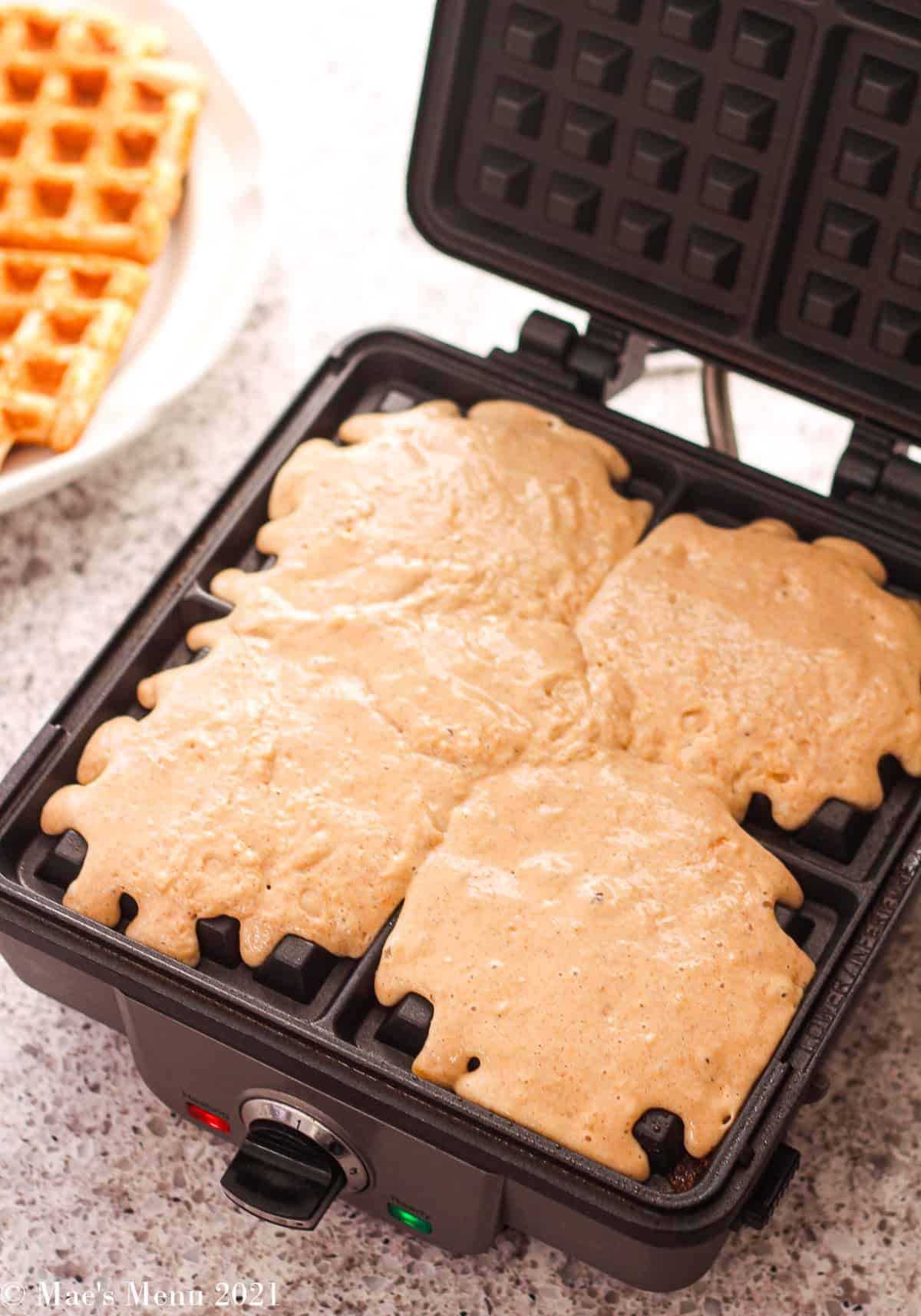 An overhead shot of a waffle iron full of batter with a waffle in the background