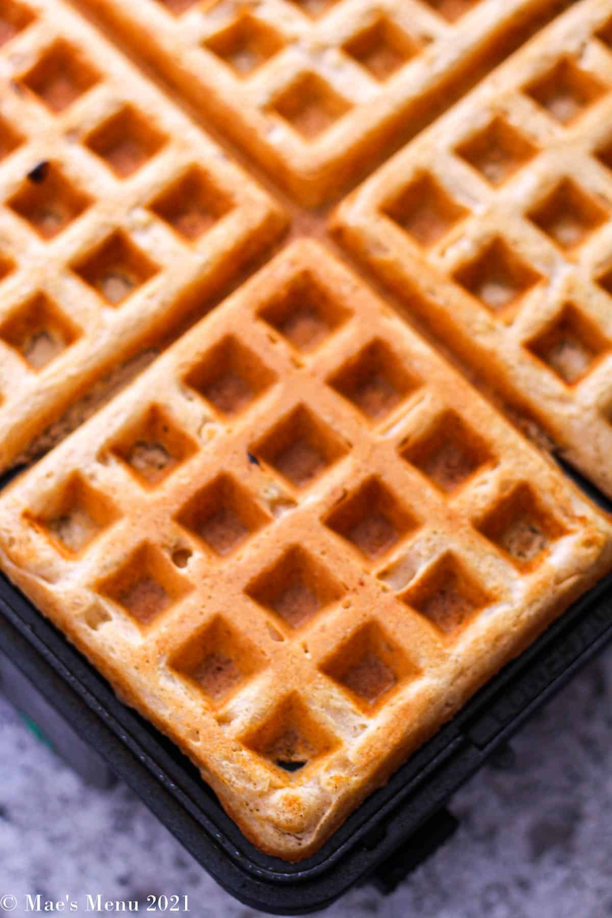An up-close overhead shot of waffles on a waffle iron