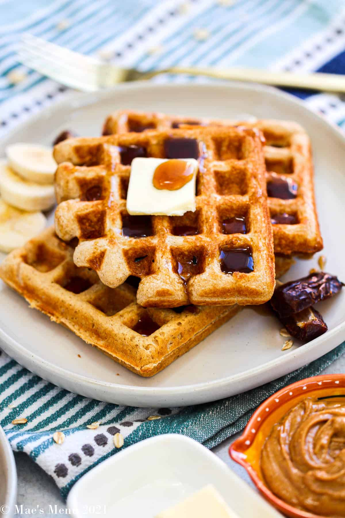 A side shot of whole wheat waffles on a white plate