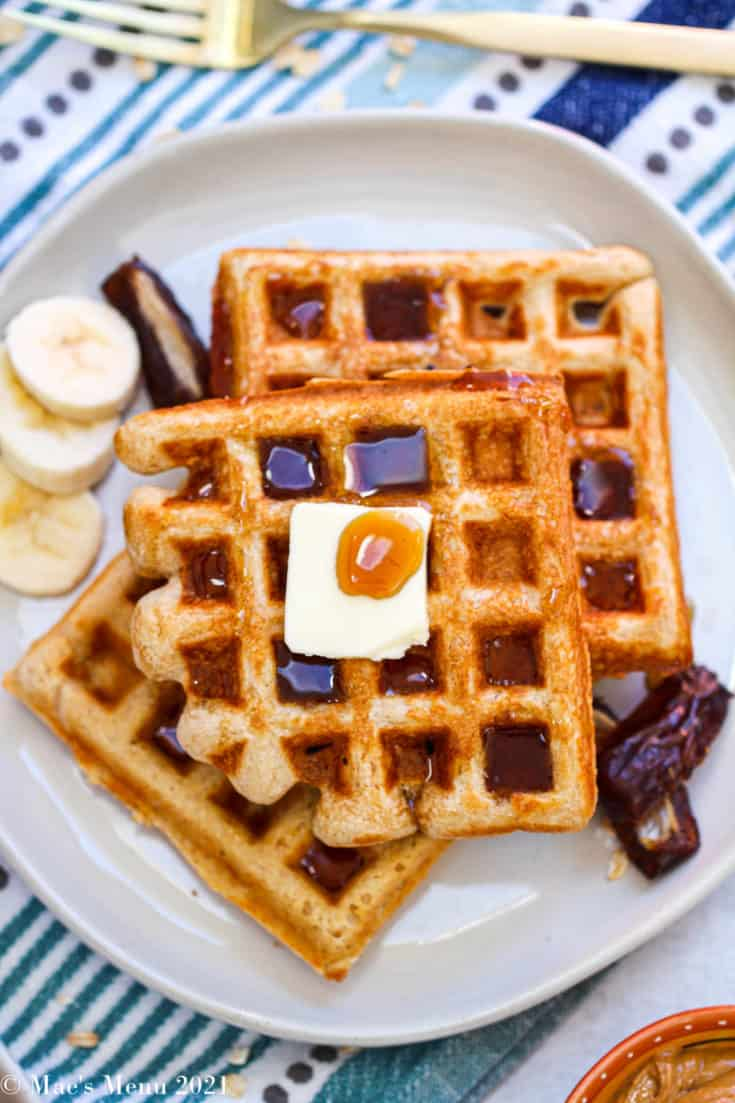 An overhead shot of a whole wheat waffle with butter, maple syrup, bananas, and dates