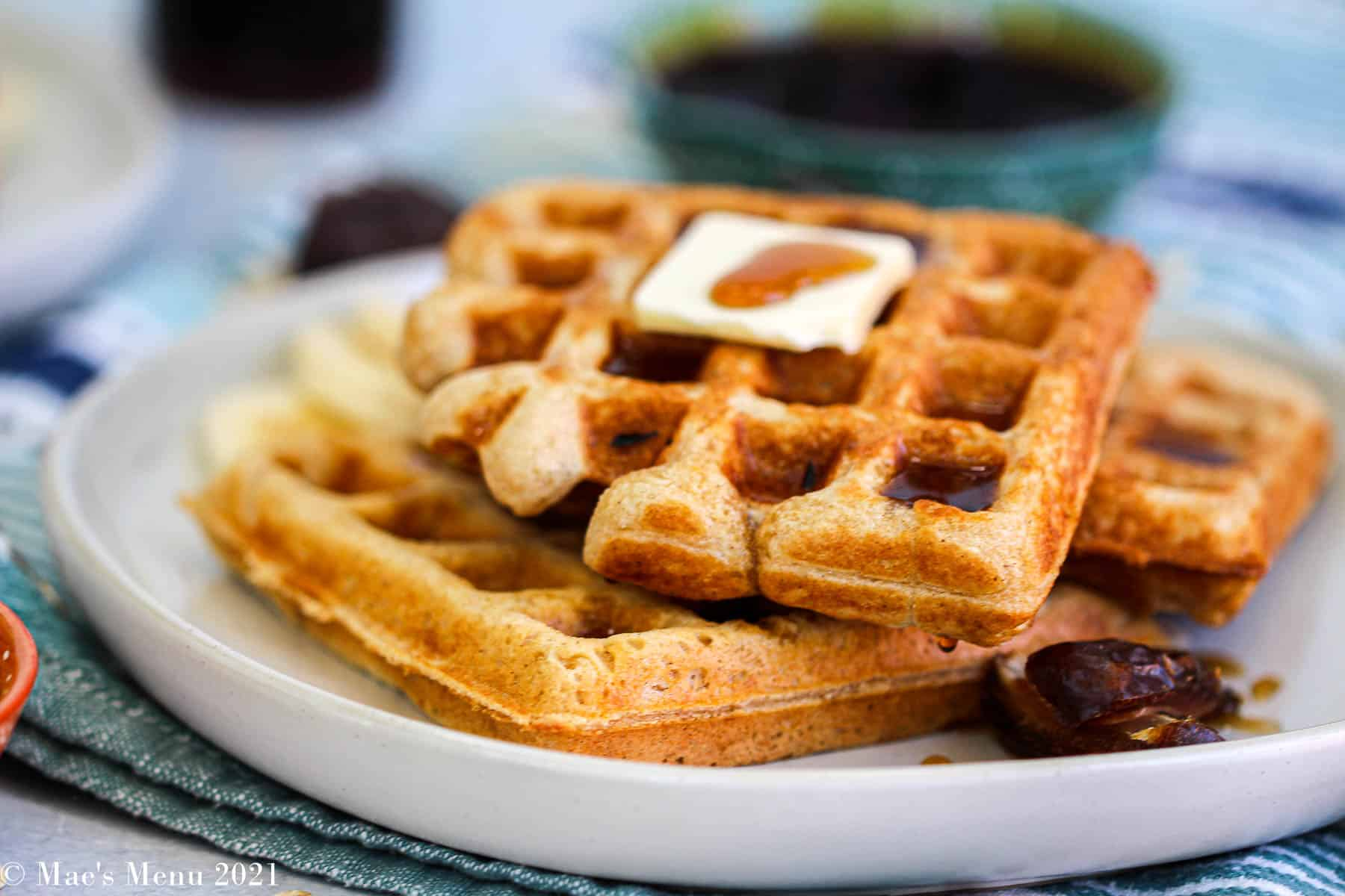 a side shot of a plate of whole wheat waffles with butter and syrup