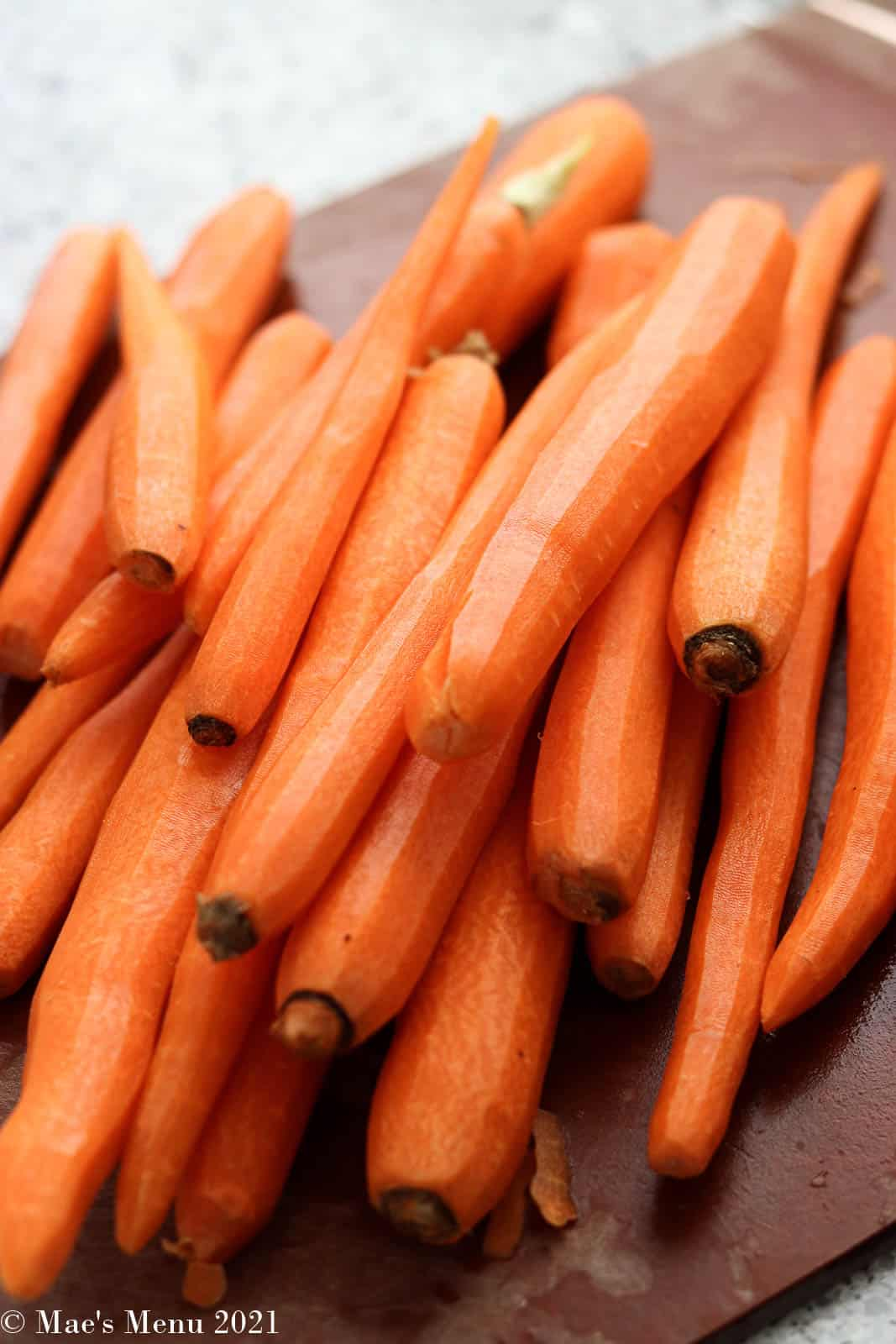 a pile of carrots on a cutting board