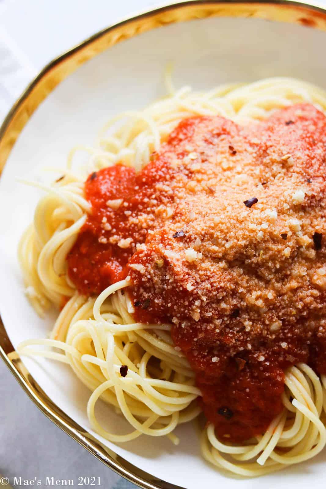 An up-close overhead shot of a dish of pasta with marinara sauce