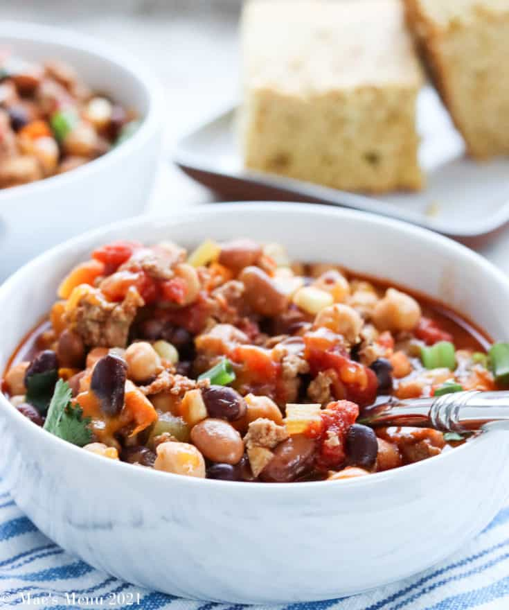 A side shot of a bowl of isntant pot turkey chili with a spoon in it