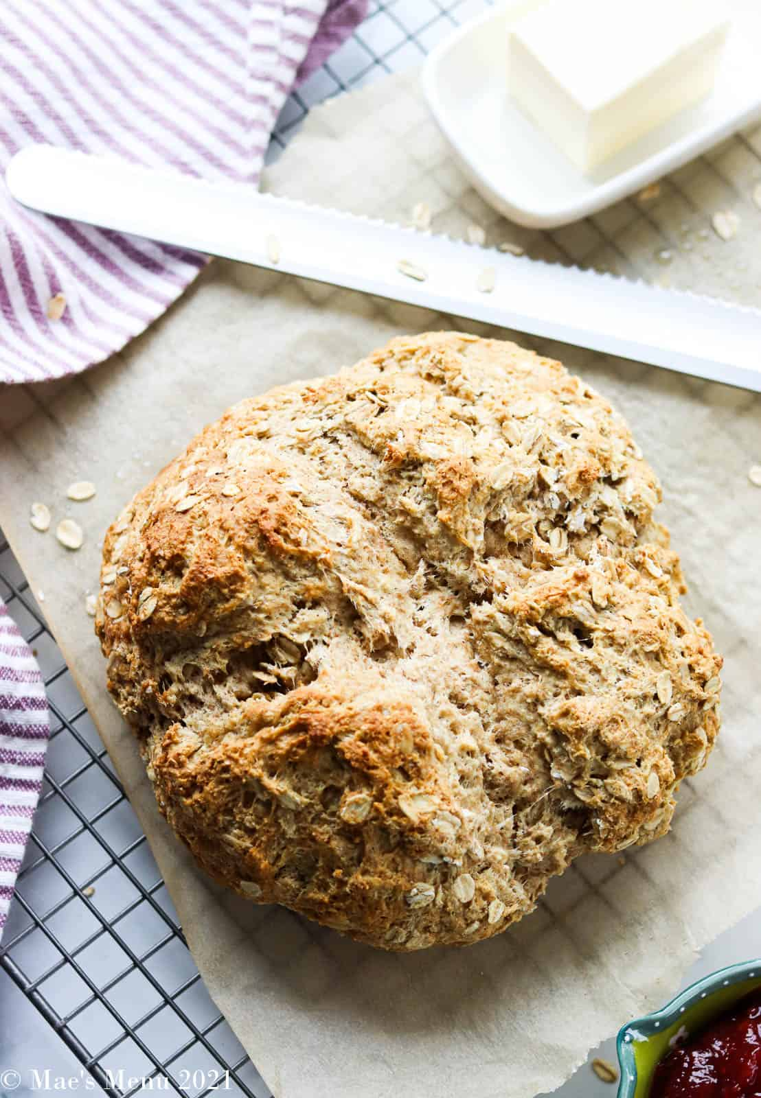A loaf of oatmeal bread surrounded by butter, jam, and a serrated knife
