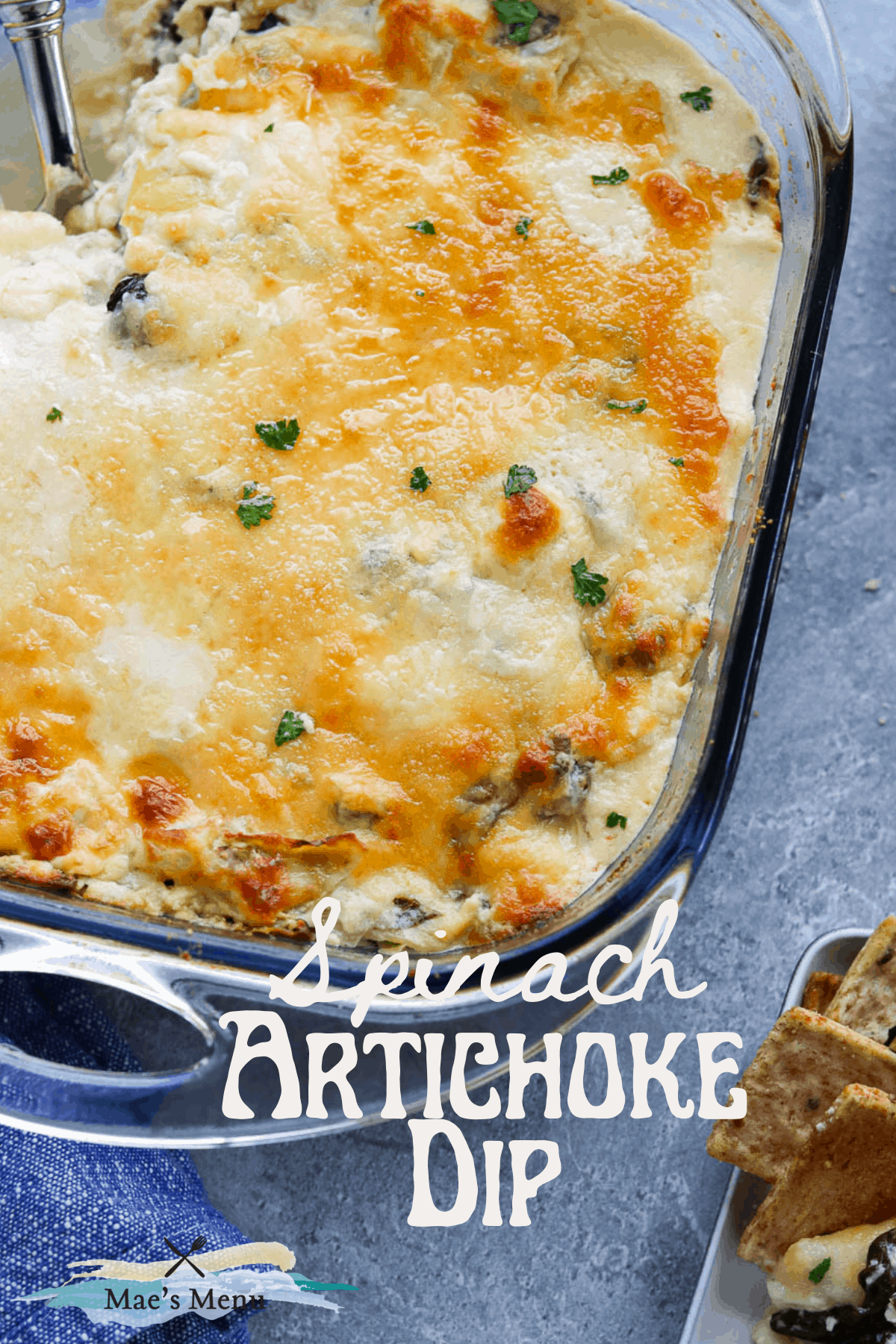 A pinterest pin for spinach artichoke dip with an overhead shot of the pan next to crackers