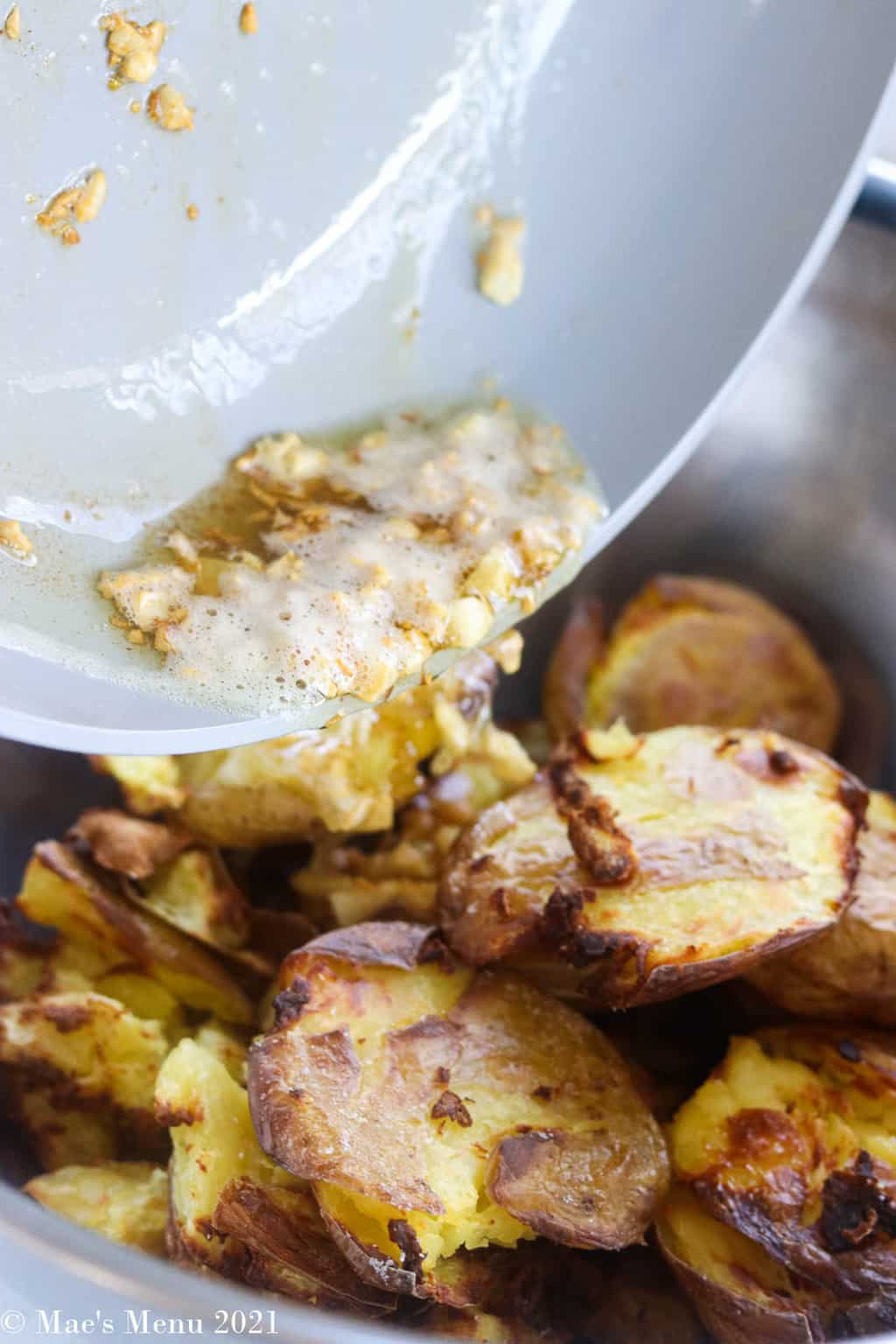 pouring garlic oil over the potatoes