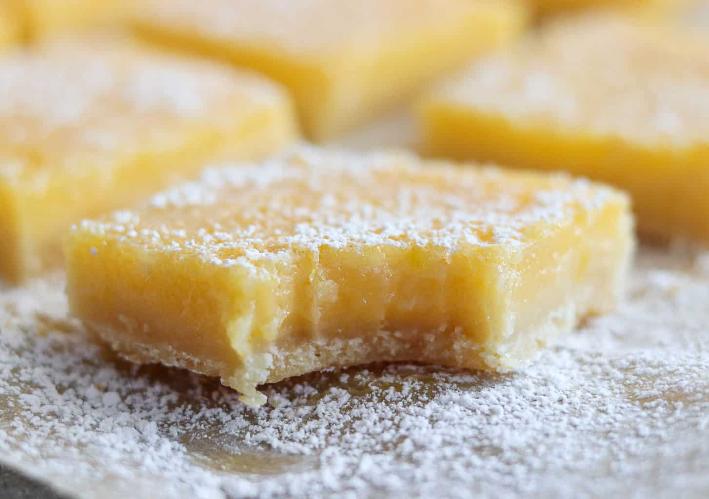 An up-close shot of a lemon bar with a bite taken out of it