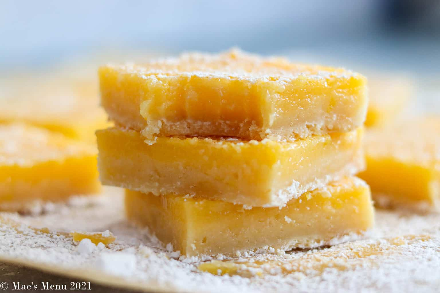 A stack of lemon bars on a sheet on parchment paper