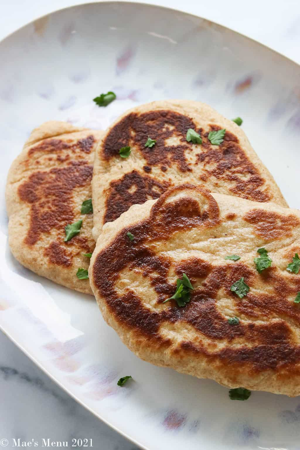 An overhead shot of whole wheat naan on a plate